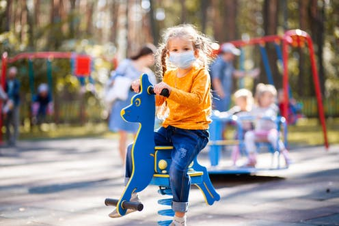 Child in playground wearing mask
