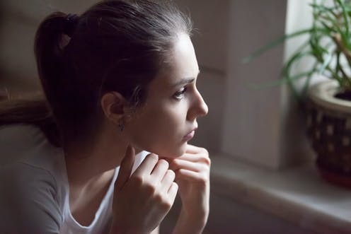 Young woman looking out a window