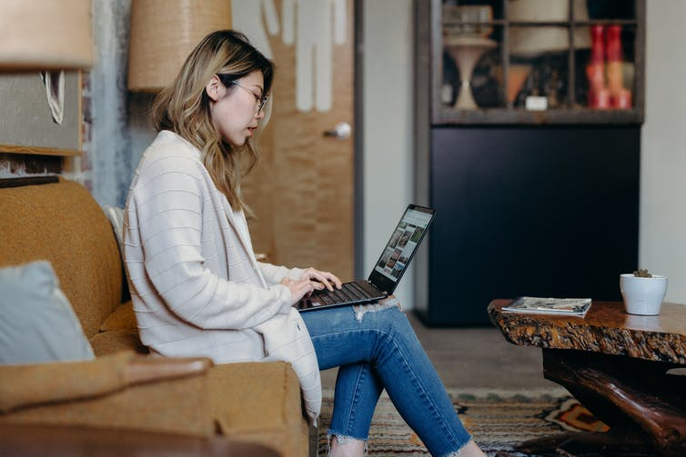 A young woman is on her laptop at home.