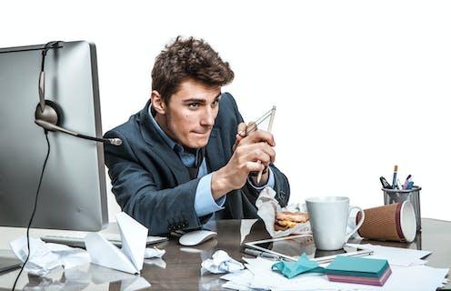 Man slacking off at work, making his pencil into a slingshot