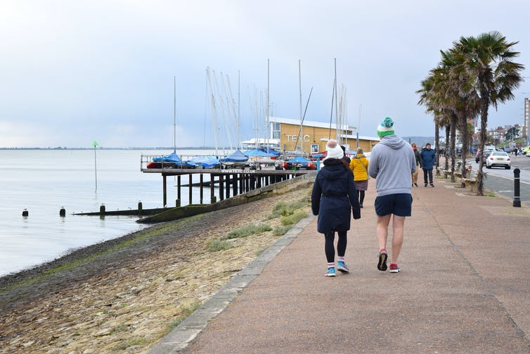 Man wearing shorts and woman wearing winter coat walking near the seaside in cold weather.