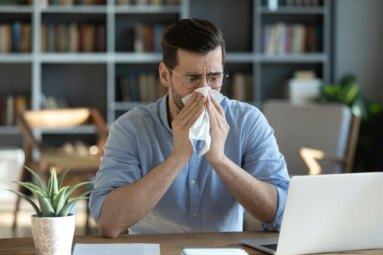 A man sitting at a desk blowing his nose with a tissue.