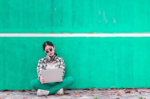 A teenager sitting against a green wall with her laptop in front of her.