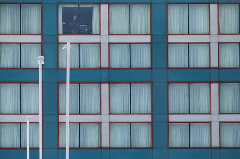 A man stands at a hotel window