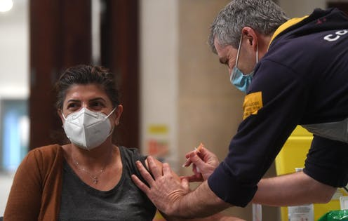 A woman in a mask being vaccinated