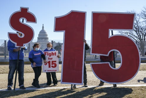 Supporters of a $15 minimum wage had up signs, including a dollar sign and the numbers one and five, with the Capitol in the background