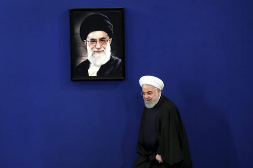 Iranian President Hassan Rouhani walks onto a stage with a portrait of the Supreme Leader Ayatollah Ali Khamenei hanging on the wall behind him.