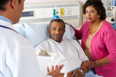 A senior couple discusses a diagnosis with a doctor.