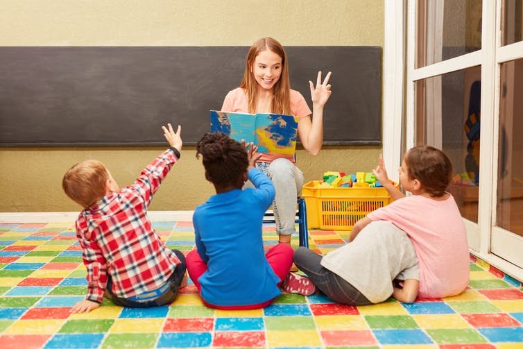 Woman reading out loud to three children in a classroom