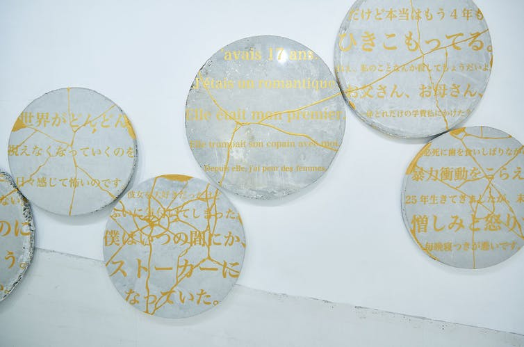 Broken plates with gold writing that have been put back togther.