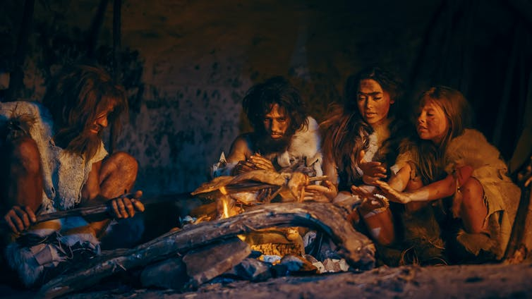 Image of early humans sitting by the fire.