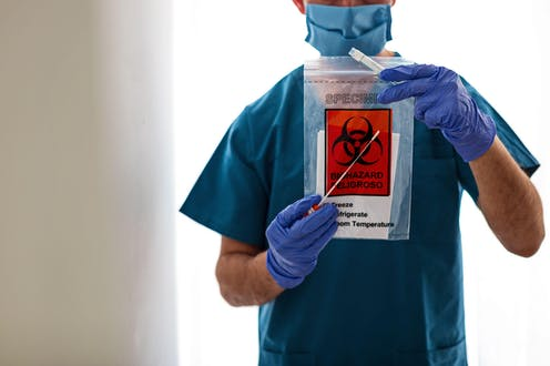 A medic holds a swab test kit up to the camera