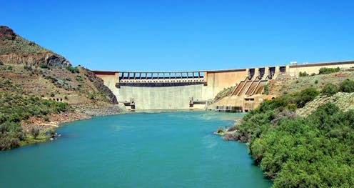 A dam in the Karoo, South Africa, surrounded by lush vegetation clear blue skies in the background.