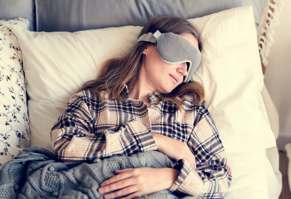 Woman napping in bed with sleep mask over her eyes.