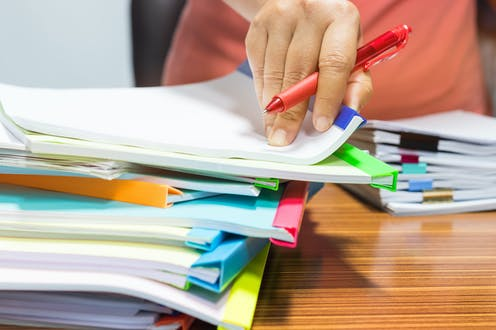 Hand with red pen and files