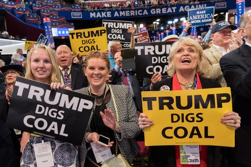 Three women hold 'Trump digs coal' signs at a rally