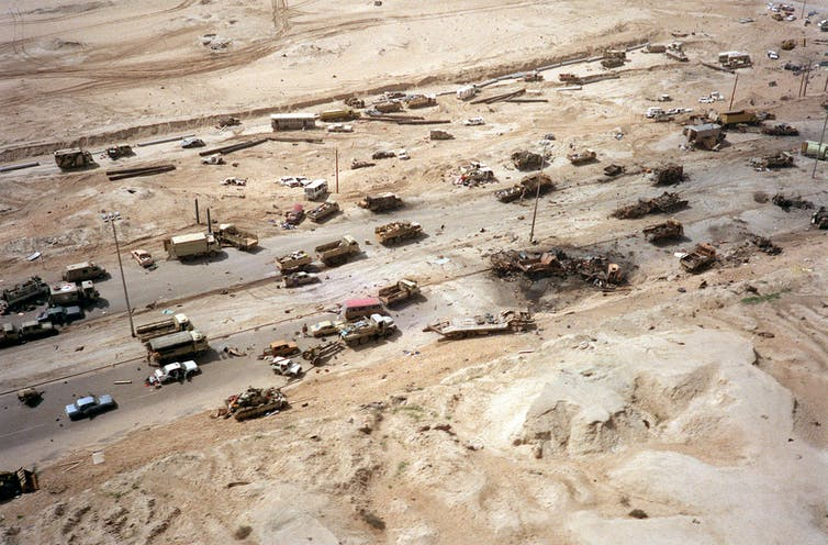 Aerial photograph of dozens of Iraqi tanks and military equipment destroyed or abandoned.