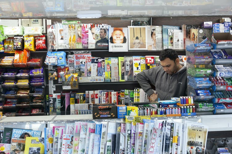 A newsagent surrounded by magazines and local papers.