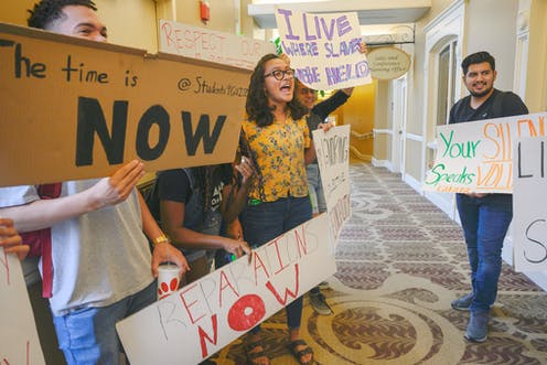 A group of students hold sign while protesting in the hallway.