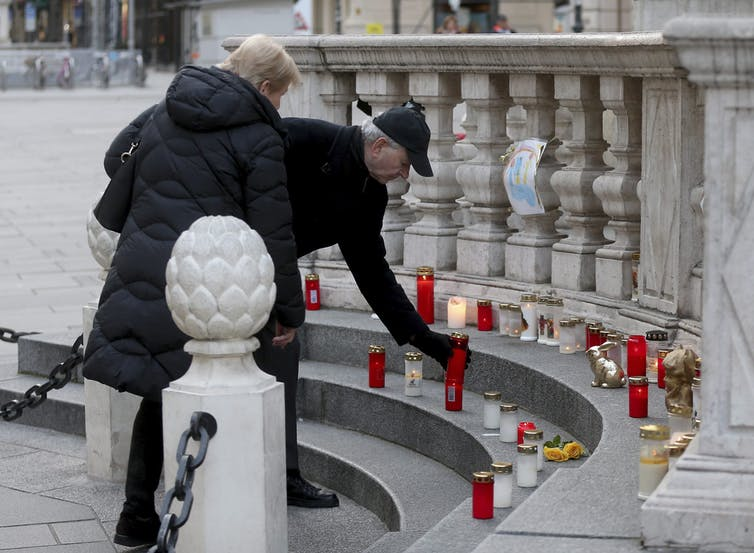 People light a candle at a plague column.