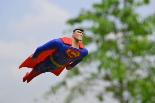 Toy Superman figurine flying past a tree.