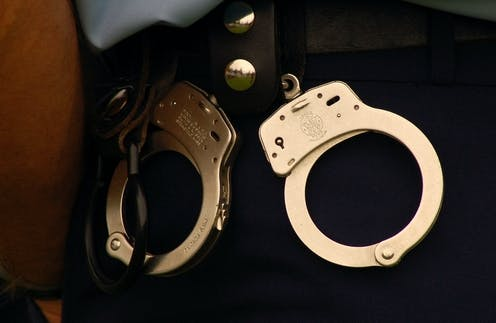 A pair of handcuffs on a New Zealand police officer's belt.
