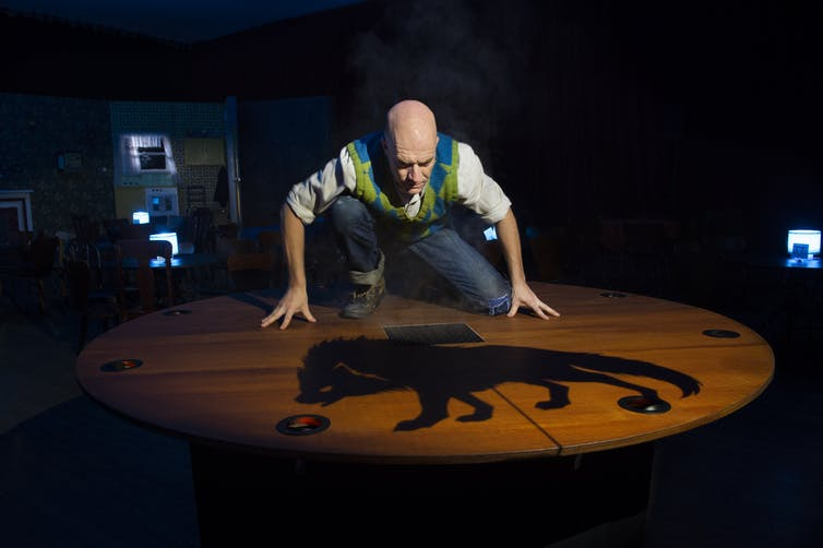 Production image: a man looks at the shadow of a dog.