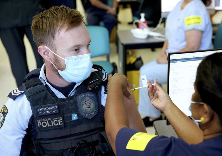 A young male police officer receives the vaccine in Sydney.