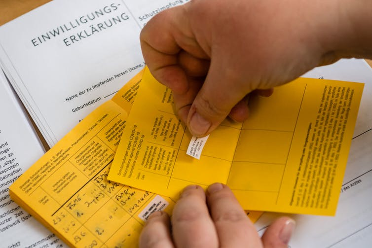 Hand applying sticker to vaccination certificate