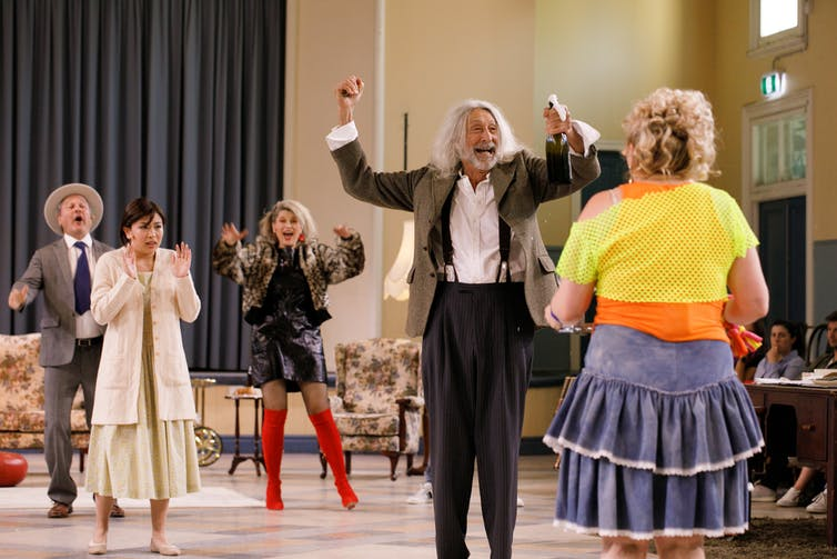Production image: the cast parties in a hall