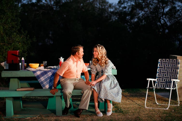 Production image: two characters in 80s dress outside.