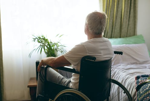 A senior man sits in a wheelchair next to a bed, looking out the window.