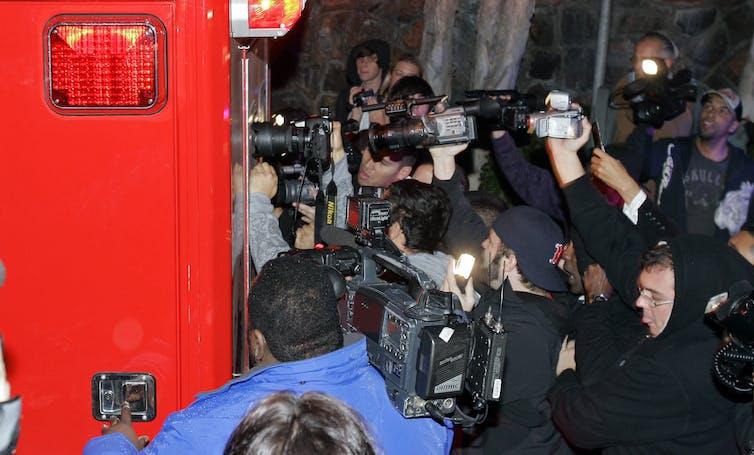 swarm of photographers around ambulance