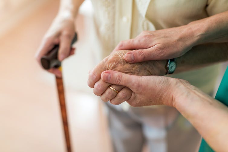 A carer holds the hand of an elderly person.