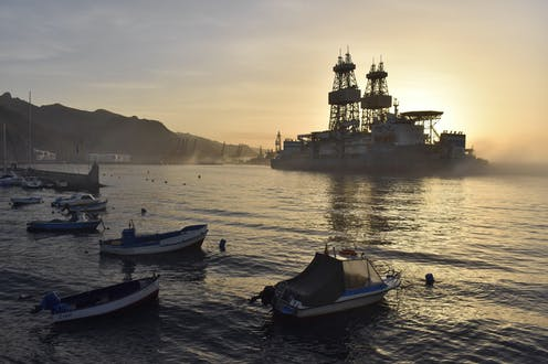 A drilling platform looms large in a calm bay with small boats in foreground.