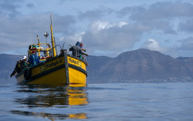 A small yellow fishing vessel sails in calm coastal waters.
