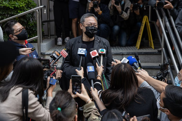 A man with a mask talking with journalists in Hong Kong.