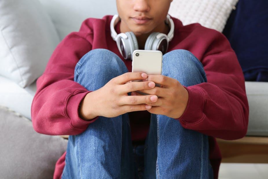 A teenage boy using a mobile phone.
