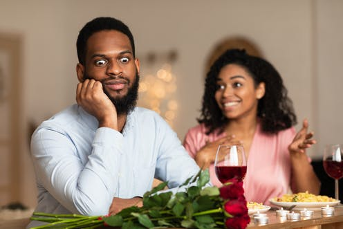 A man looks away from a speaking women with an amusing expression of boredom