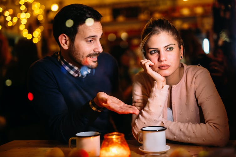 A man appears to be boring a woman in conversation in a bar