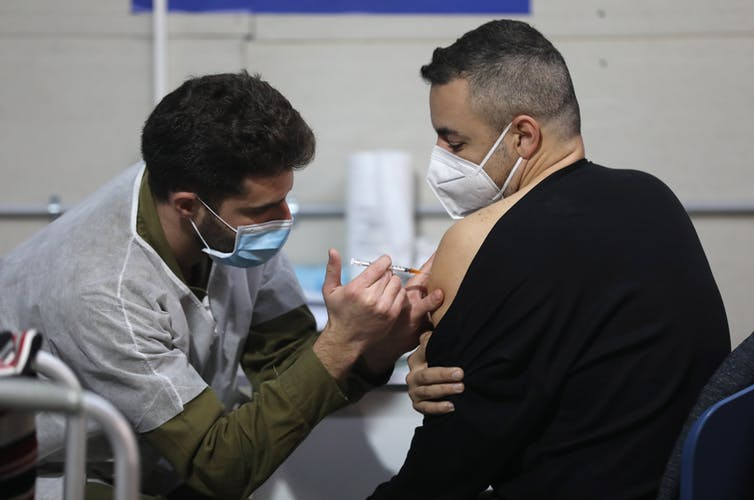 A man wearing a COVID mask getting vaccinated