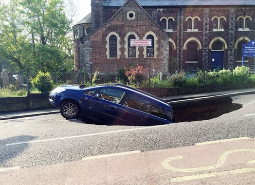 A blue car falling into a sinkhole in the road. Church in background.