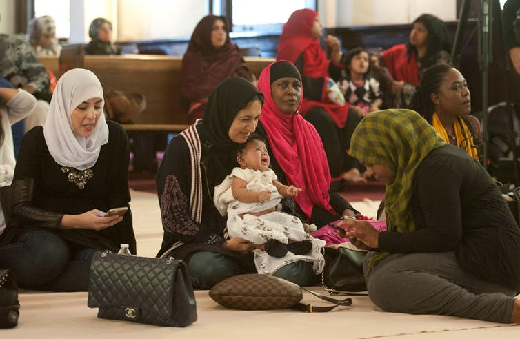 Muslim women and a baby waiting for prayer service in mosque while sitting on the floor