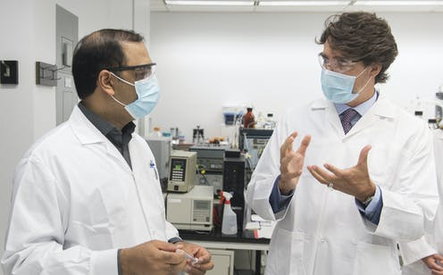 A scientist with Justin Trudeau in facemaks.s