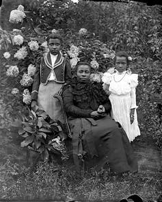 A woman poses with her stylishly dressed daughters in a lush garden.