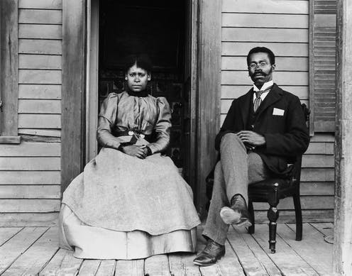Betty and Willis Coles pose on a porch sitting in chairs.