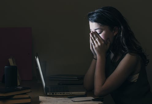A young woman horrified at what she sees on her computer.