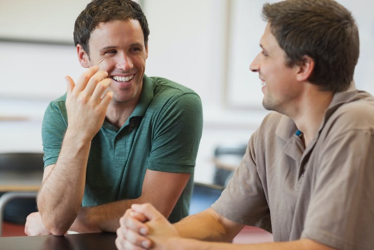 Two young male students smiling and chatting