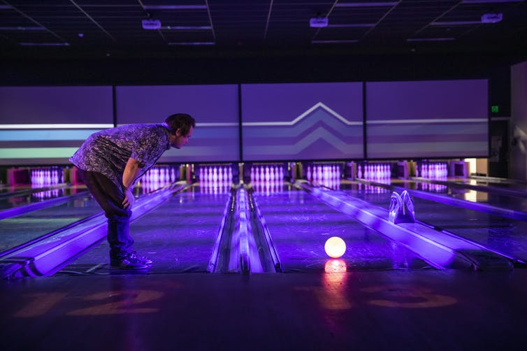 A man leans over a glowing bowling ball.