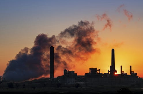 Coal fire power station silhouette against a sunset
